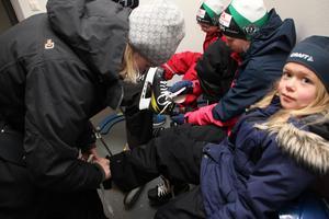 Marika Hagelberg knyter skridskor åt Vilma och Julia. Lillebror Oskar får hjälp av pappa Anders.