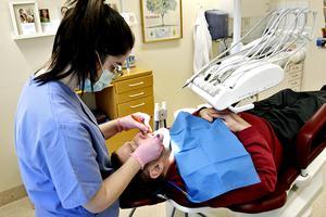 Tandhygienisten Joana Henriques från Portugal trivs på sitt nya jobb vid folktandvården i Matfors. Här hjälper hon 75-årige Jonny Solberg med en kontroll av tandhälsan.