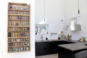 Samlingen av souvenirglas på väggen och köket i svart med bänkskivor i betong.