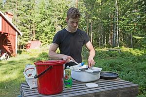 Simon visar också hur han just nu diskar ute på en enkel diskbänk av trä som står utomhus i skogsbrynet. Det är torpets enda vattenkälla just nu.