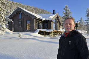 Peter  Daun på Slagga framför ett nyproducerat fritidshus på Himmelfjäll.