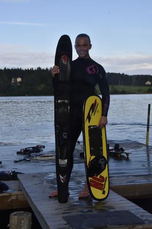 Jane poserar med sin utrustning - den gula skidan till höger används i grenen trick och den svarta till vänster till slalom.