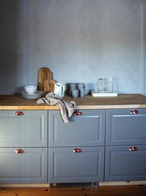 Värmen i köket kommer ifrån trägolvet och beslagen i mässingsfärg medan den gråa väggnyansen är kall.
