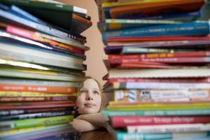 En flicka tittar på staplar med barnböcker. Foto: Jessica Gow / TT /