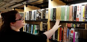 Emelie Lindström visar Elena Ferrantes böcker som finns på listan över mest utlånade böcker inte bara i Södertälje.