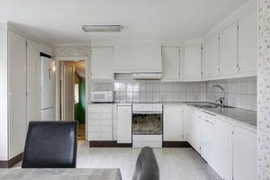Köket har kakel ovanför köksbänkarna och plats för matbord och stolar.Foto: Svensk Fastighetsförmedling.