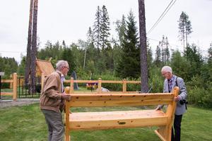 Göran Nilsson och Göthe Falkman, bär en kyrkbänk som de själva har snickrat.