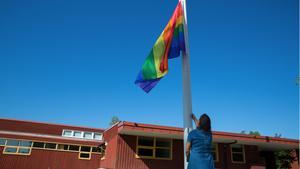 Sylvia Krenn, tillförordnad utbildningschef på Nykvarn kommun, hissar regnbågsflaggan på Turingeskolan.