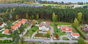 Gästhemmet Furuhaga är till salu, bakom tallarna skymtar Tegera arena. (Foto: Eric Böwes, Svensk fastighetsförmedling)