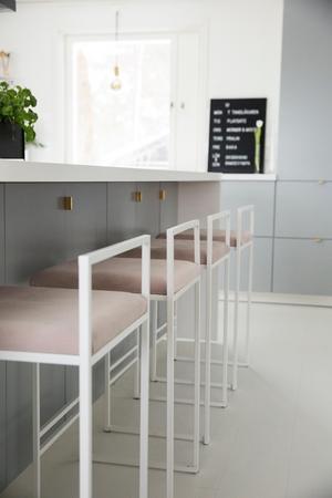 Vid den stora köksön sitter man på fina höga barstolar med rosa sammetssits från byCrea.