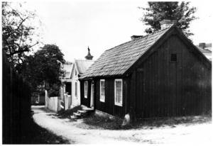 Stora Bergsgränd 5, den Wennmanska släktgården. Backen leder ner till Nedre Bergsgatan. I ett rum till vänster om ytterdörren bodde August och Lova med sönerna John och Olle. Till höger om dörren hade pojkarnas faster ett rum. Fönstret närmast kameran hörde till ett så kallat kallrum, beboeligt sommartid. Denna del av Stora Bergsgränd försvann i Södersaneringen.