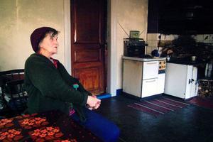 Göta Olsson på sin favoritplats, i köket vid bordet och där hon kan öppna dörren till kammaren och se på tv:n som står där inne. Till höger den sparsamt använda elspisen och den ständigt varma vedspisen som har en benägenhet att ryka in. Foto: Ingvar Ericsson