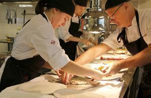 Peter Abrahamsson hjälper Johanna Larsson att lägga upp maten innan servering.
