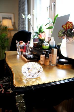 I vardagsrummet står ett ommålat bord i rokokostil, där Gunmari bland annat har sitt smink.