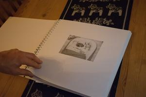 Björn bläddrar igenom ett album om Nannie. På bilden har hon somnat in.