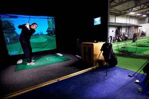 """Sören Westin och Oskar Olsson flyr kylan till förmån för Hawaii och golfbanan Kapalua med hjälp av Golfhallens golfsimulator. """"Vi glömde att ta med shortsen"""" skojar Oskar Olsson. Sören Westin lägger upp bollen """"pin-high""""  på den korta par-3:an i bästa Ernie Els-stil.Foto: Håkan Luthman"""