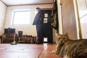 Katten Tristan håller ordning på Djupvikens gård i Torsåker. I bakgrunden syns ägaren Jonas Halonen.