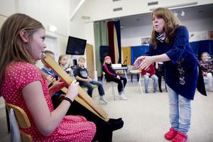 Musiklärare Kerstin Samnell instruerar Judith och hennes kompisar på basflöjt att komma in rätt på sin del i låten Eld och vatten.