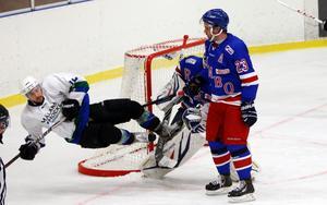 Rimbo Hockeys Mattias Lundblad tittar på när Mälarös Zachary Joy tar sig en flygtur.