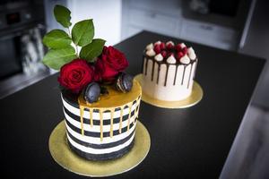 Chokladtårtan med hallon innehåller hallonkompott, mörk chokladmousse, hallonganasch och devils cake. Den randiga är en salted caramel cake med marängsmörkräm, daim, saltkolasås och sockerkaksbotten. Rosor, macarons och droppande guldchoklad på toppen.