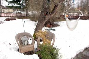 En inredd vrå i trädgården sticker upp ur snön.