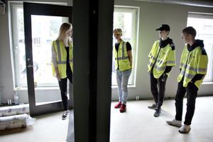 Kalle Porath, Liam Berglund och Petter Oldberg visas runt av  Anna Podgorsek.