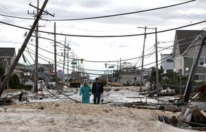 Några vandrare på sönderslagna Route 35 i Seaside Heights, New Jersey, efter orkanen Sandy. Fler våldsamma stormar är att vänta när temperaturen stiger.