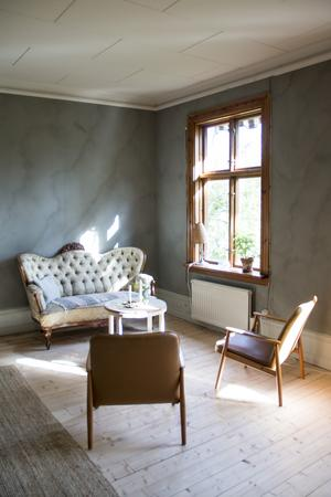 En soffa i nyrokoko ståtar i salens ena hörn.