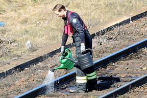 Vattenkannor är de släckredskap som krävs för att komma till rätta med denna lilla brand, intill rälsen.