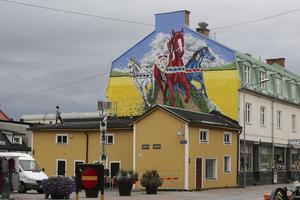 21 september. Som en del i firandet av Ludvika stad 100 år smyckades husgaveln vid Garvarns torg med en stor väggmålning. Uppe på taket ses konstnären Shai Dahan nöjt blicka upp mot sina färggranna dalahästar – som också har hyllats stort av allmänheten.
