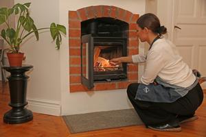 Med 400 kvadratmeter att värma upp behövs alla tillgängliga värmekällor. Alice Genberg tänder en brasa på övervåningen.