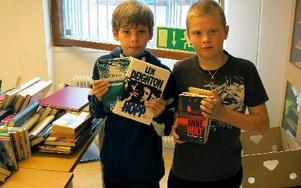 Ett helt bord fullt med böcker. Tim Eriksson och Victor Embretsen håller upp någraav böckerna som sak säljas på loppisen. FOTO: ILSE BRATTLÖF