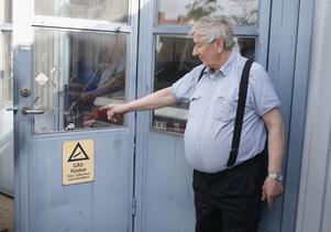 Stig Pettersson visar den dörr där tjuvarna tog sig i vid bilfirman natten till torsdag.
