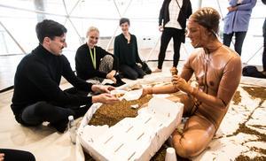 Performancen är interaktiv; här erbjuds en man i publiken att mata maskarna med kyckling.