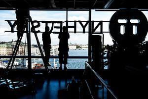 TT, Tidningarnas Telegrambyrå, har utsikt över centrala Stockholm från sin adress på Katarinavägen. På  bilden byter TT ut sin gamla logotyp i Glashuset i samband med namnbytet till TT Nyhetsbyrån. Det skedde 2013, samma år som företagt lämnade Norrland.  Foto: Vilhelm Stokstad / TT /