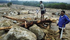 Thailändare i provinsen Krabi tittar på skadorna orsakat av allt regn.  Foto: AP Photo/Sumeth Parnpetch/Scanpix