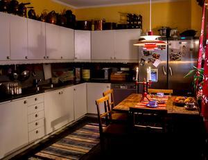 I köket sprakar elden i vedspisen och samlandet syns även här. Kopparkittlar och bakformar står uppradade.