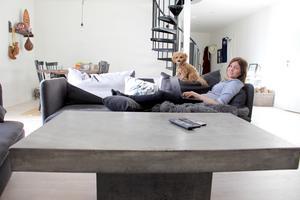 Hårt soffbord och mjuk soffa. Hon ligger gärna i soffan tillsammans med Pysen och skriver.