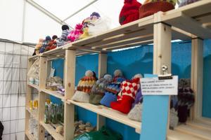 I butiken i lägret kan man handla stickade mössor som församlingar runt om i Sverige har stickat och donerat.