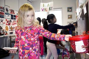 Myra Adamsson väljer pepparkakor i barnens mataffär på Norra Vallbyskolan.