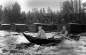 En annan farlig del av flottningsarbetet var att åka utför forsar med båt. Bilden är från Ljusnan 1955. Flytvästar började inte användas av flottare förrän på 1960-talet men var aldrig populära eller väl använda. Simkunnigheten var inte heller stor i yrkeskåren.