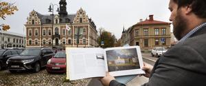 Lars Nylander med sin bok om Söderhamn, som innehåller Albert Blombergssons målning av det gamla rådhuset i Söderhamn.