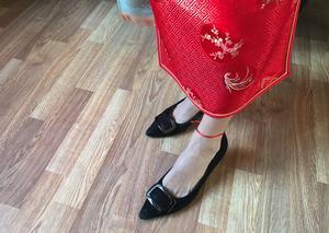 För att få bra hälsa och lycka hela året ska man helst bära något rött, i alla fall om man är född under grisens år. Det räcker med ett litet rött band. Louise Jian Hua visar hur hon knutit sitt runt vristen.