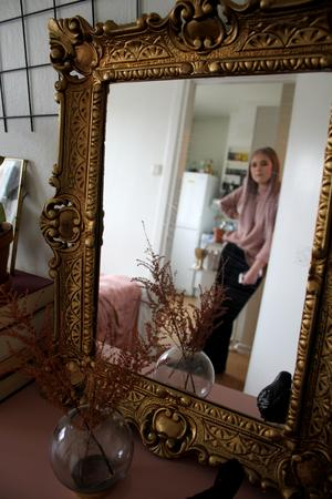 Guldspegel och en vas med torkad astilbe.