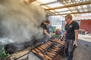 På senare år så har man börjat röka annat, som räkor, musslor och pepparlax. Här kollar Nils Ehnberg och Per Sjöbom till den rökta rödingen.
