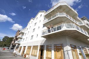 Hamnhus 1 består av två vita huskroppar och ett med rödbrunt tegel. Fram till i mitten av oktober pågår inflyttningarna. En port i taget. På första våningen, ovanför blivande restaurangen, har Elisabeth Stenberg och Kent Norberg precis flyttat in.