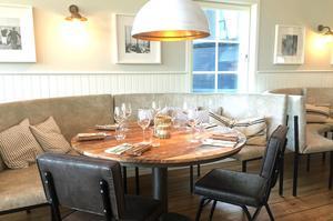 Rå träkänsla i de stavlimmade borden bryter av mot strama soffgrupper och stolar. Matsalen har fått en avslappnad och inbjudande atmosfär.