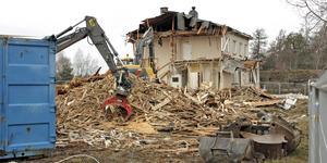 Halva byggnaden har redan rivits, och blivit till högar av trävirke och annat bråte.