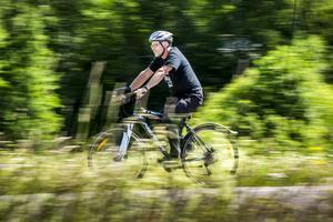 Bengt Moberg störs inte särskilt av regn under cykelturen, kanske förbannar han naturen lite, innan han tar på sig en regnkappa.