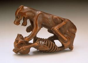 En hund våldför sig på ett människoskelett. Klassisk japansk netsuke med nekrofili motiv.